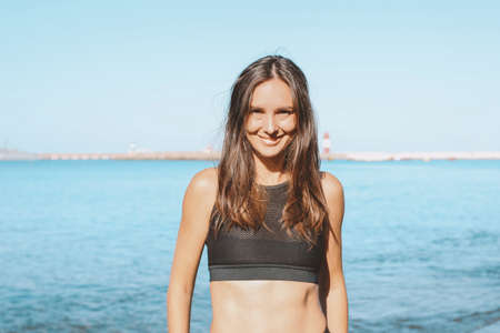 Young slim athletic long hair smiling woman in the sportswear on the sea beach, healthy lifestyle Stock Photo