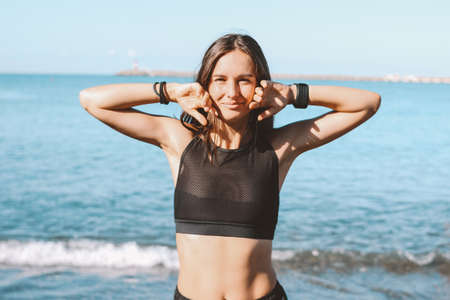 Young slim athletic long hair sensual woman in sportswear on the sea beach in morning, healthy lifestyle Stock Photo