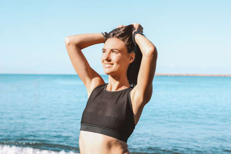 Young slim athletic long hair sensual woman in sportswear on the sea beach in the morning, healthy lifestyle