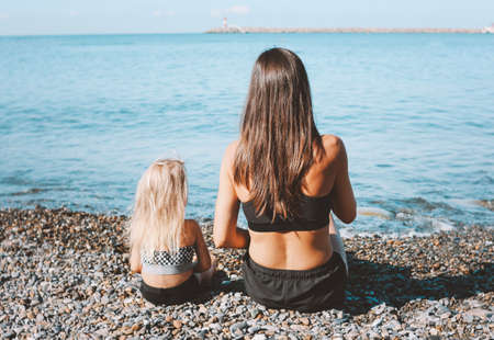 Young fit woman mom with little cute girl sitting on the beach together, healthy lifestyle, sport family