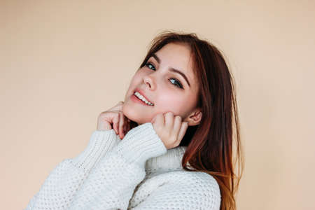 Portrait of beautiful smiling teenager girl with clean skin and dark long hair in cozy white sweater on the beige background Zdjęcie Seryjne