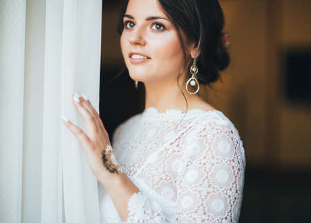 Beautiful smiling bride brunette young woman in white lace dress near the window, close up Zdjęcie Seryjne