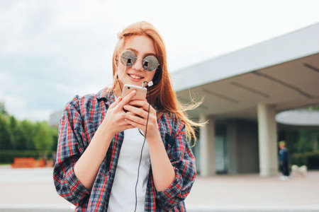 Attractive redhead smiling girl in round sunglasses with phone in her hands in casual clothes listening music on street in the city Zdjęcie Seryjne