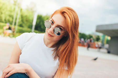 Attractive redhead smiling girl in round sunglasses in casual clothes sitting on street in the city