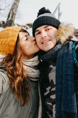 The happy couple in love making selfie at forest nature park in the cold season. Travel adventure love story