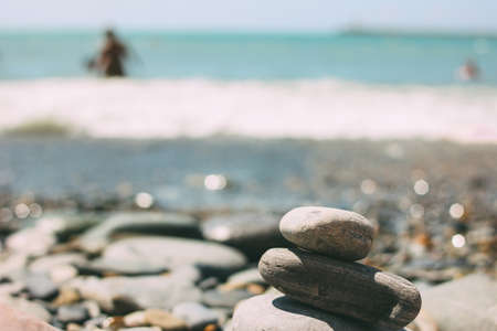 Pile of pebbles stones on the blurred sea beach background