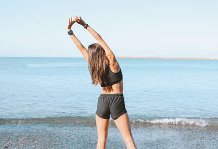 Young slim athletic long hair woman in sportswear doing exercises on the sea beach in the morning, healthy lifestyle