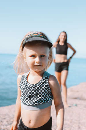 Little cute girl looking at camera on background of fit mom on the beach, healthy lifestyle, sport family Stock Photo