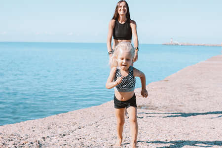 Little cute girl running from fit mom on the beach, healthy lifestyle, sport family