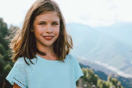 Smiling tween girl looking at camera on the background of beautiful mountains, family travel concept adventure lifestyle