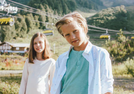 Children brother and sister friends look up with admiration against the background of mountain resort, family travel