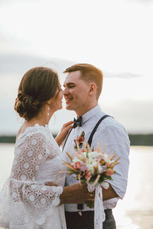 Happy newly married couple, smiling bride brunette young woman with the boho style bouquet with groom, close up portrait outdoors