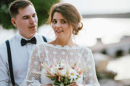 Happy newly married couple, smiling bride brunette young woman with boho style bouquet with groom, close up portrait outdoors