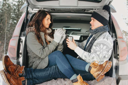 The happy couple in love in trunk of car at forest nature park in the cold season. Travel adventure love story