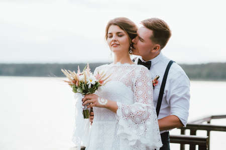 Happy newly married couple, smiling bride brunette young woman with boho style bouquet with groom, outdoors