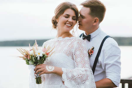 Happy newly married couple, smiling bride brunette young woman with the boho style bouquet with groom, outdoors