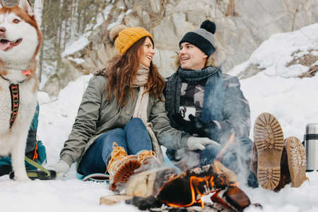 The happy couple with dog haski at the forest nature park in the cold season. Travel adventure love story Фото со стока