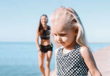 Linda niña corriendo para adaptarse a mamá en la playa, estilo de vida saludable, deporte familiar