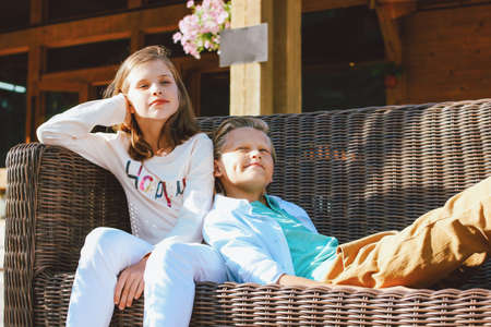 Attractive preteen children sister and brother, friends sitting on wicker sofa in backyard of the wooden cottage 写真素材