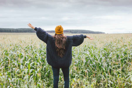 Beautiful carefree long hair asian girl in the yellow hat and knitted sweater from behind in the autumn corn field. Sensitivity to nature concept Фото со стока