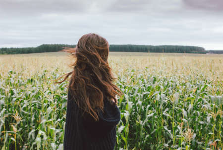 Beautiful carefree long hair asian girl in knitted sweater in the autumn corn field. Sensitivity to nature concept
