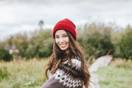 Beautiful carefree long hair asian girl in the red hat and knitted nordic sweater in autumn Фото со стока