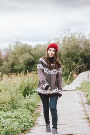 Beautiful carefree long hair asian girl in red hat and knitted nordic sweater in autumn nature park Фото со стока