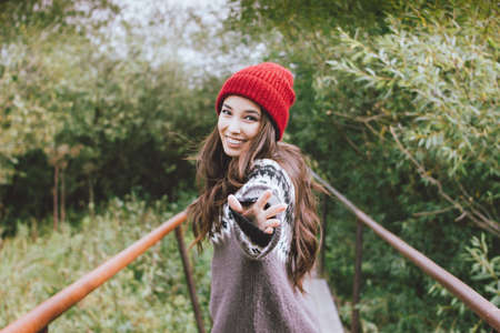 Beautiful carefree long hair asian girl in the red hat and knitted nordic sweater in autumn nature park Фото со стока