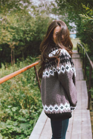 Beautiful carefree long hair asian girl in knitted nordic sweater in the autumn nature park