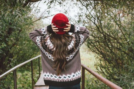 Beautiful carefree long hair asian girl in the red hat and knitted nordic sweater in autumn nature park, travel adventure lifestyle