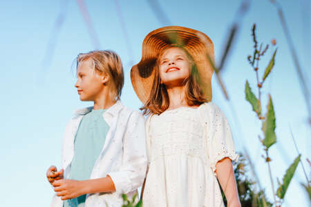 Laughing children brother and sister friends in grass on the background of blue sky, rural scene Stock fotó