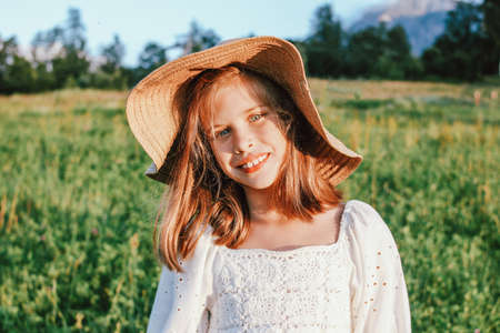 Beautiful romantic preteen girl in straw hat against the background of beautiful houses in mountain, rural scene at sunset, golden hour