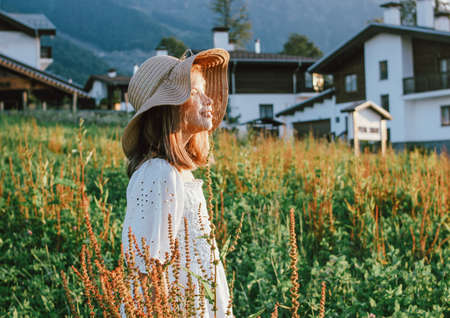Beautiful romantic preteen girl in straw hat against the background of beautiful houses in the mountain, rural scene at sunset. View from behind, golden hour Banco de Imagens