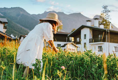Beautiful romantic preteen girl in straw hat picking flowers against the background of beautiful houses in the mountain, rural scene at sunset