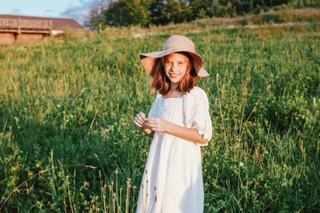 Beautiful romantic preteen girl in white dress and straw hat at the meadow, golden hour