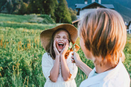 Laughing children friends at the green meadow, rural scene. Boy gives flowers, first love