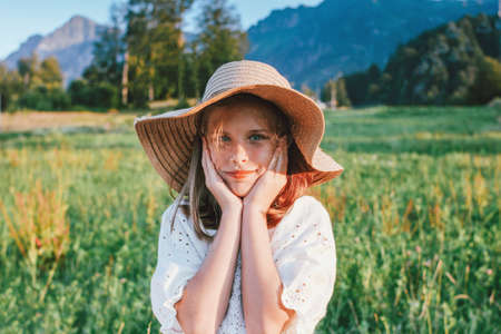 Beautiful romantic preteen girl in straw hat against the background of mountains, golden hour Banco de Imagens