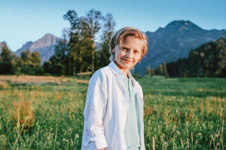Blonde smiling boy looking at camera on background of wonderful view of green meadow and mountains, family travel adventure lifestyle Banco de Imagens