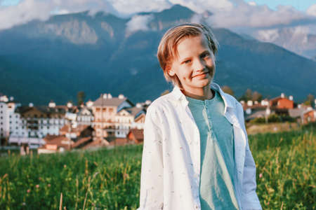 Blonde smiling boy looking at camera on background of wonderful view of mountain resort, family travel adventure lifestyle Banco de Imagens - 129802107