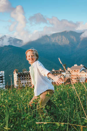 Blonde smiling boy looking at camera on background of wonderful view of mountain resort, family travel adventure lifestyle