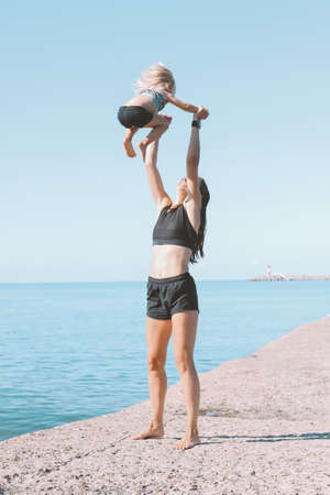 Young fit woman mom with little cute girl exercising on beach together, healthy lifestyle, dynamic gymnastic Banco de Imagens