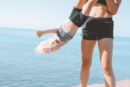 Young fit woman mom with little cute girl exercising on the beach together, healthy lifestyle, dynamic gymnastic