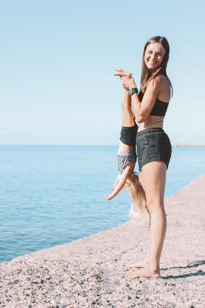 Young fit woman mom with little cute girl exercising on the morning beach together, healthy lifestyle, sport family