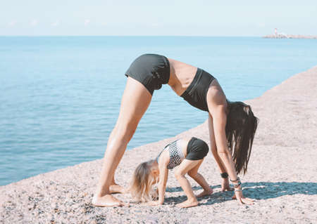 Young fit woman mom with little cute girl exercising on morning beach together, healthy lifestyle, sport family Banco de Imagens
