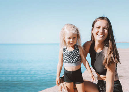 Young fit woman mom with little cute girl exercising on sea beach together, healthy lifestyle