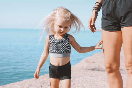 Little cute girl looking at camera on background of fit mom on the beach, healthy lifestyle, sport family Banco de Imagens