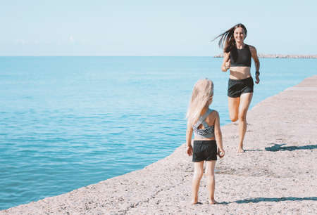 Little cute girl looking to fit mom on the beach, healthy lifestyle, sport family