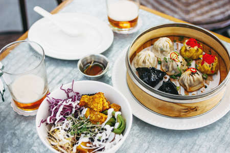 Pan-Asian food - different dim sums in a bamboo bowl and salad. Lunch for two with beer Stockfoto