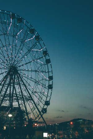 Glowing lights on the Ferris wheel, resort nightlife, background, beautiful sky. High iso, grain Stock Photo