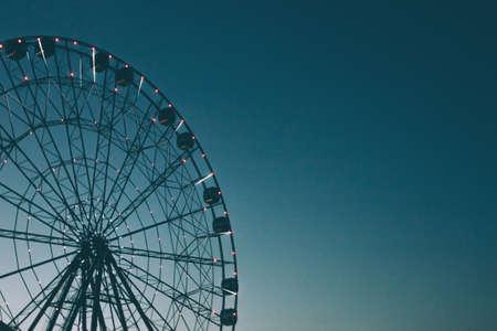 Glowing lights on the Ferris wheel, resort nightlife, background, beautiful sky. High iso, grain Banco de Imagens